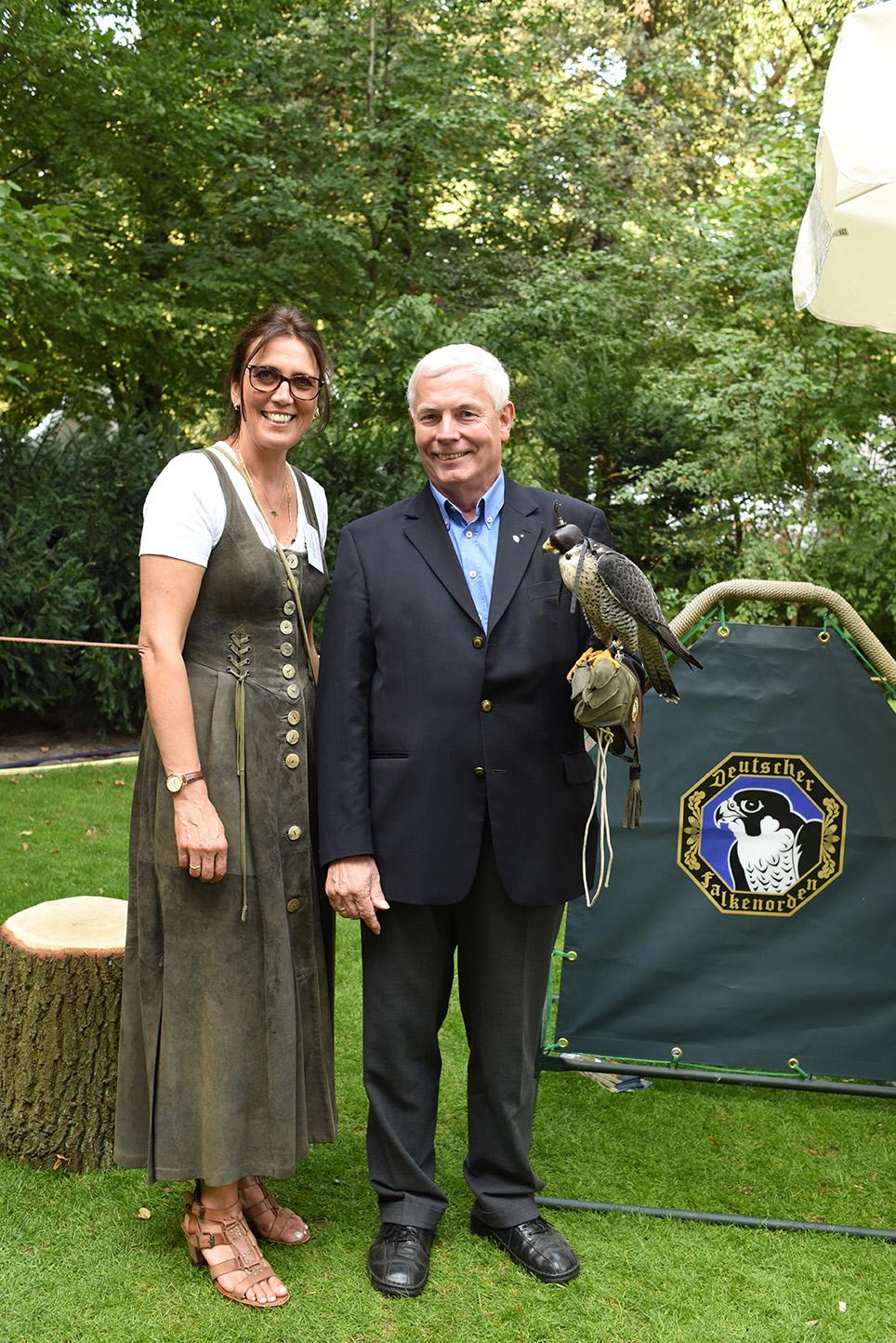 Norbert Leben posiert neben einer Falknerin mit Falke auf dem Arm
